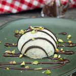 A serving of pistachio semifreddo dessert, sprikled with chopped pistachios and drizzled with dark chocolate.
