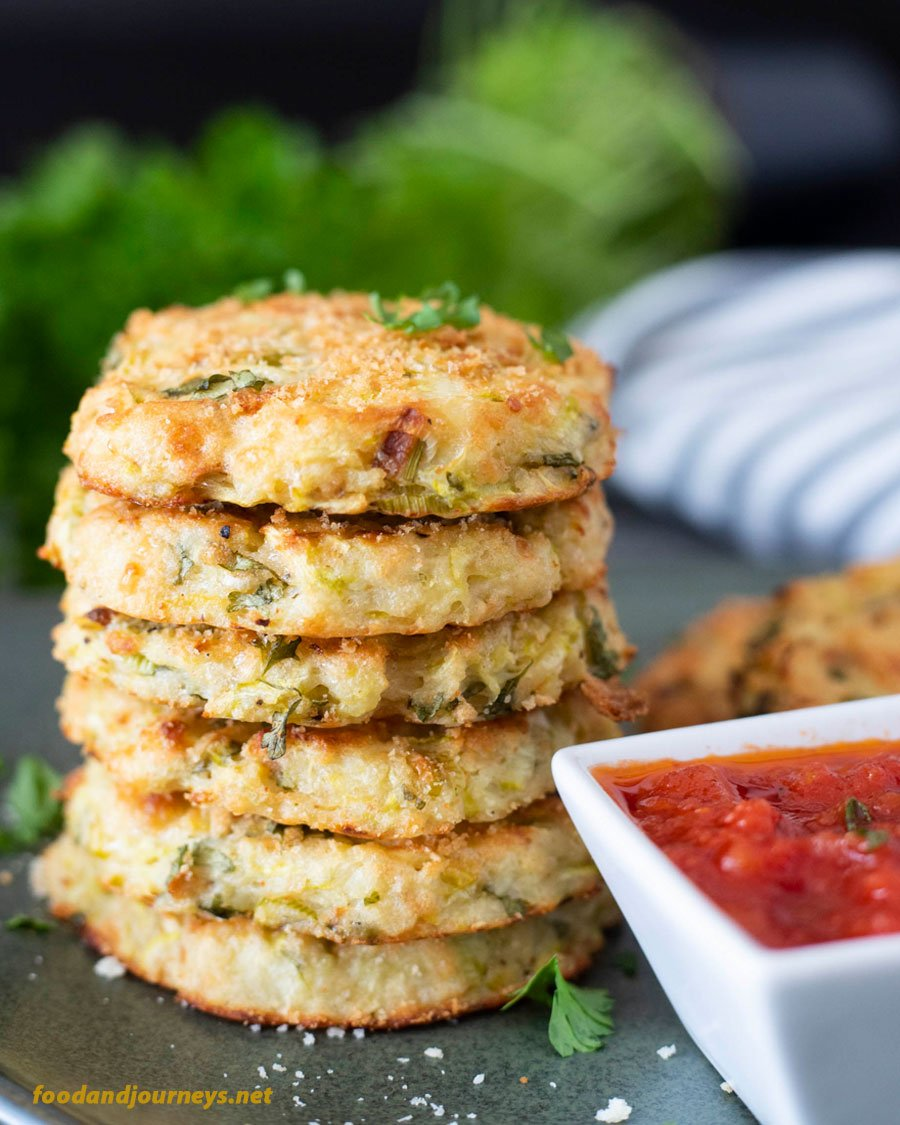 A stack of baked potato and zucchini bites, with some marinara sauce on the side. Bits and pieces of grated zucchini and some herbs are visible in every piece. There's equal amount of potatoes and zucchini in each bite, a healthy appetizer than can also be served as snack!