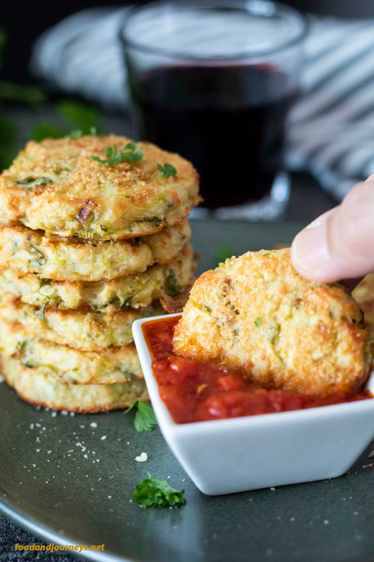 A piece of baked potato and zucchini bite being dipped in marinara sauce, with more fritters served on the plate. These bites are an even better version of mashed potato pancakes; each fritter does not only contain mashed potato, but grated zucchini, parmesan and herbs as well. All of which are clearly visible in this image.