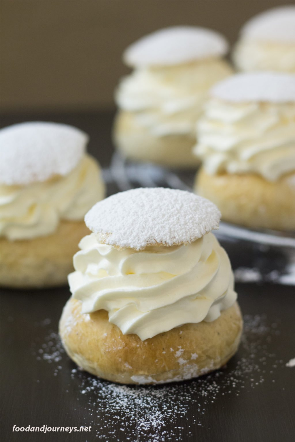 Closer shot of a piece of Swedish Lent Buns (Semlor), highlighting whipped cream and powdered sugar on top.