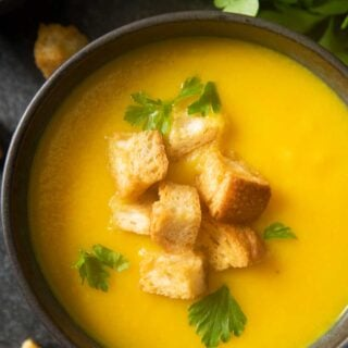 An overhead shot of a bowl of yellow pepper soup, garnished with croutons and fresh parsley.
