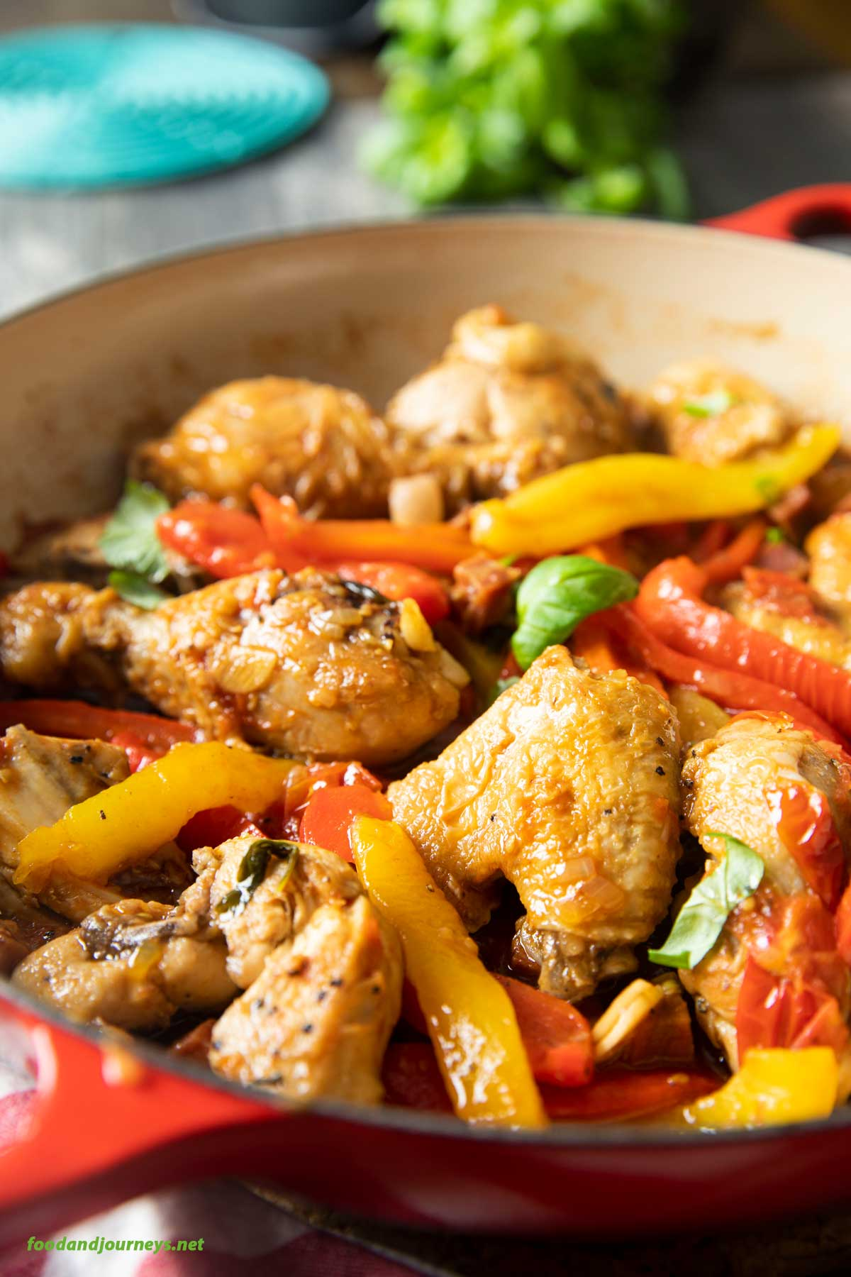 A closer shot of a pan of chicken alla romana, highlighting the peppers and juicy chicken.