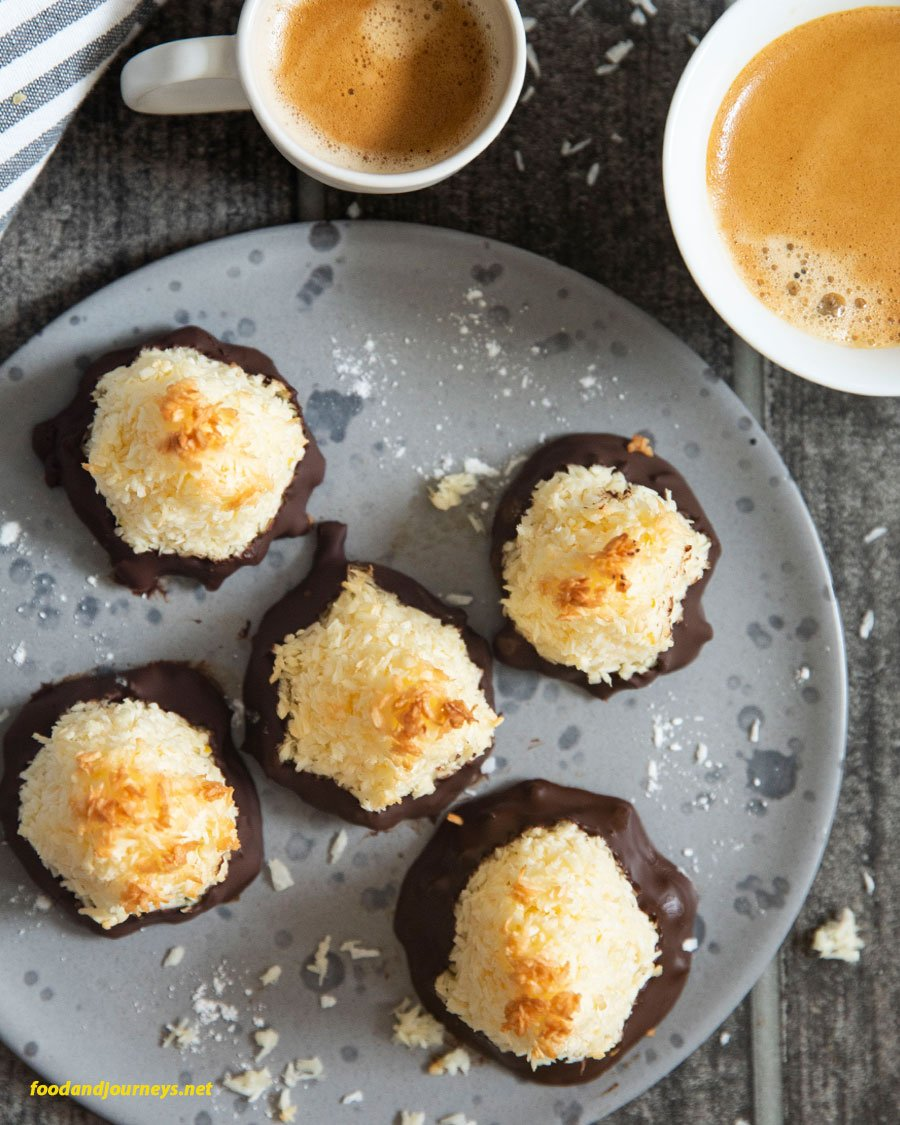 An overhead shot of a plate of Swedish Coconut Bites, served with a cup of coffee and espresso.
