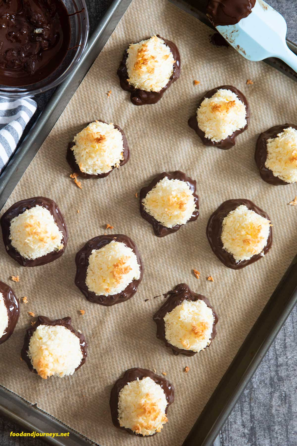 An overhead shot of a baking tray, lined with baking paper, filled with Swedish Coconut Bites, waiting for the chocolate to solidify.