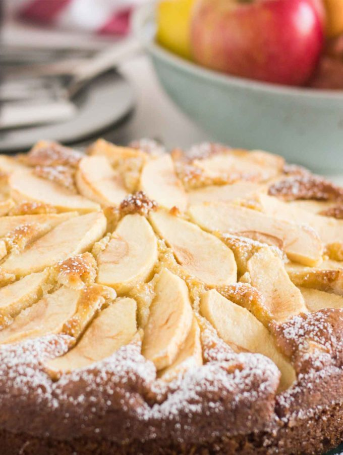 A side shot of an entire Tuscan Apple Cake, showing a bowl of apples in the background and a glass of sweet wine.