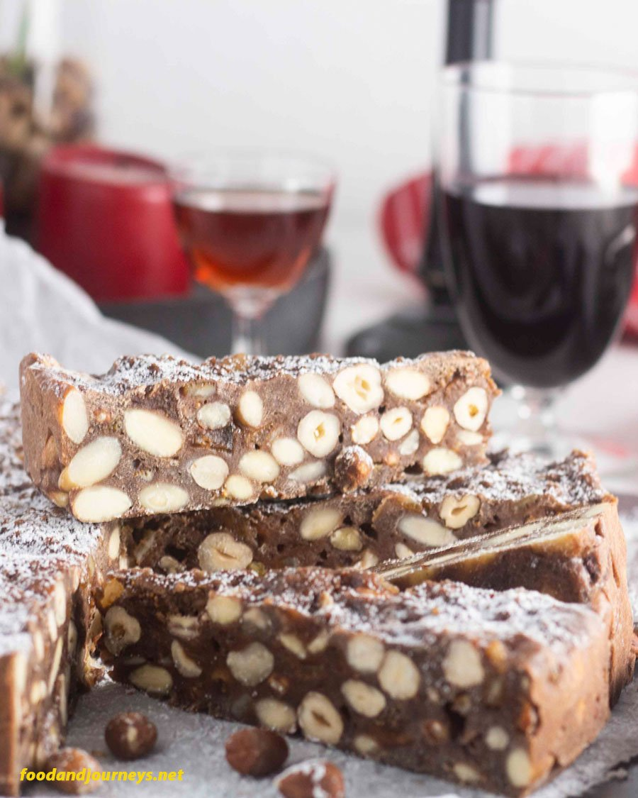 Image showing slices of Panforte, highlighting the nuts and dried fruits inside, served with red and sweet wine.