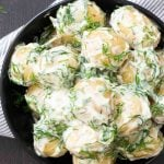 An overhead shot of Swedish Potatoes with Dill Cream Sauce. For this particular image, new potatoes were used, and the skin of the potatoes were left on them. The dill cream sauce can be used with grilled salmon or other grilled meat as well.