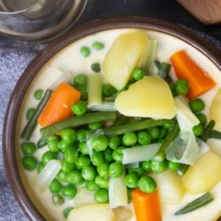 An overhead shot of a serving of Finnish Summer Soup, with a chunk of blue cheese and a glass of white wine on the side.