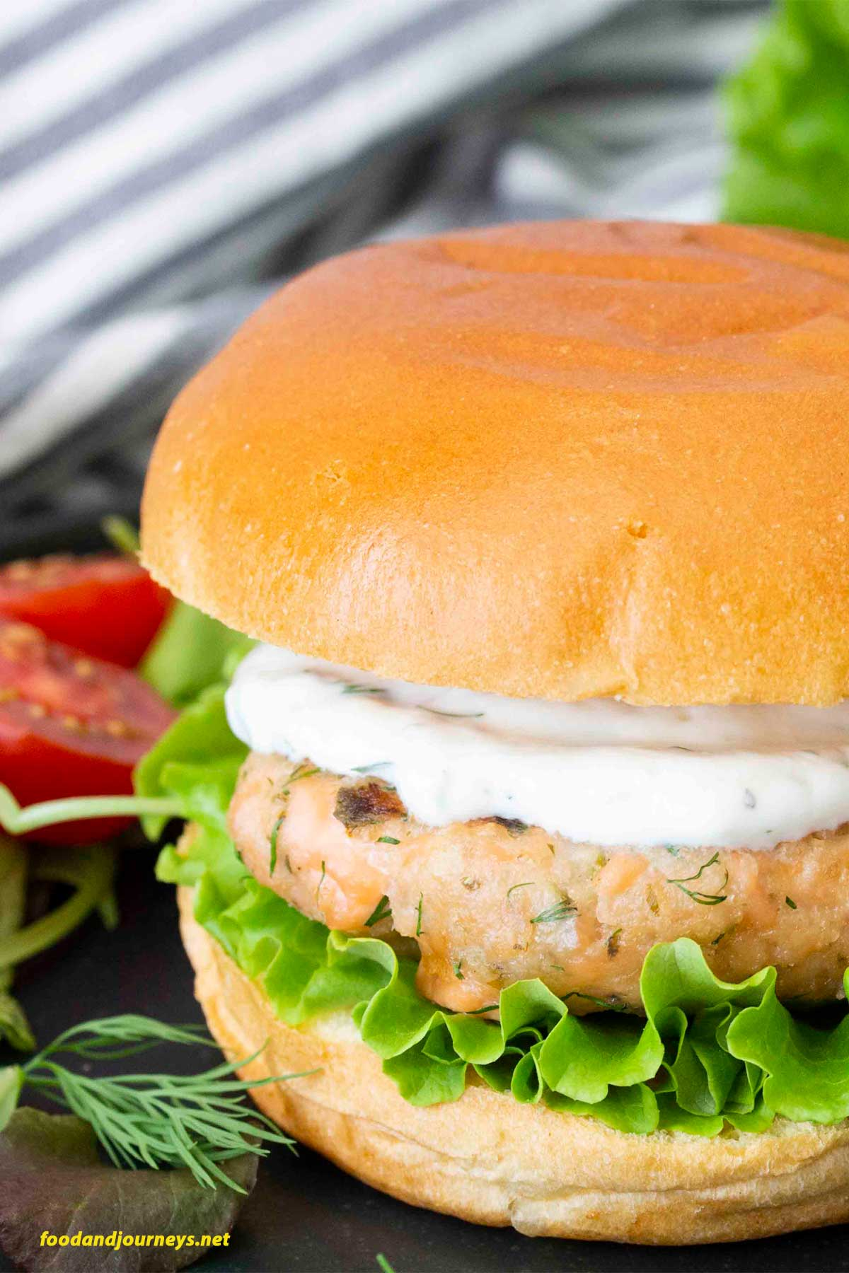 A closer shot of Swedish Salmon Burger, highlighting the bits of salmon in the patty, as well as the lemon yogurt sauce.