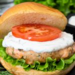 An image showing how to serve a Swedish Salmon Burger, tomatoes and lettuce were added to the burger and lemon yogurt sauce.