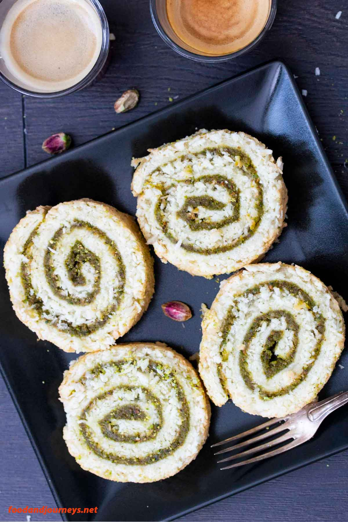 Overhead shot showing four slices of Coconut & Pistachio Cake Roll.