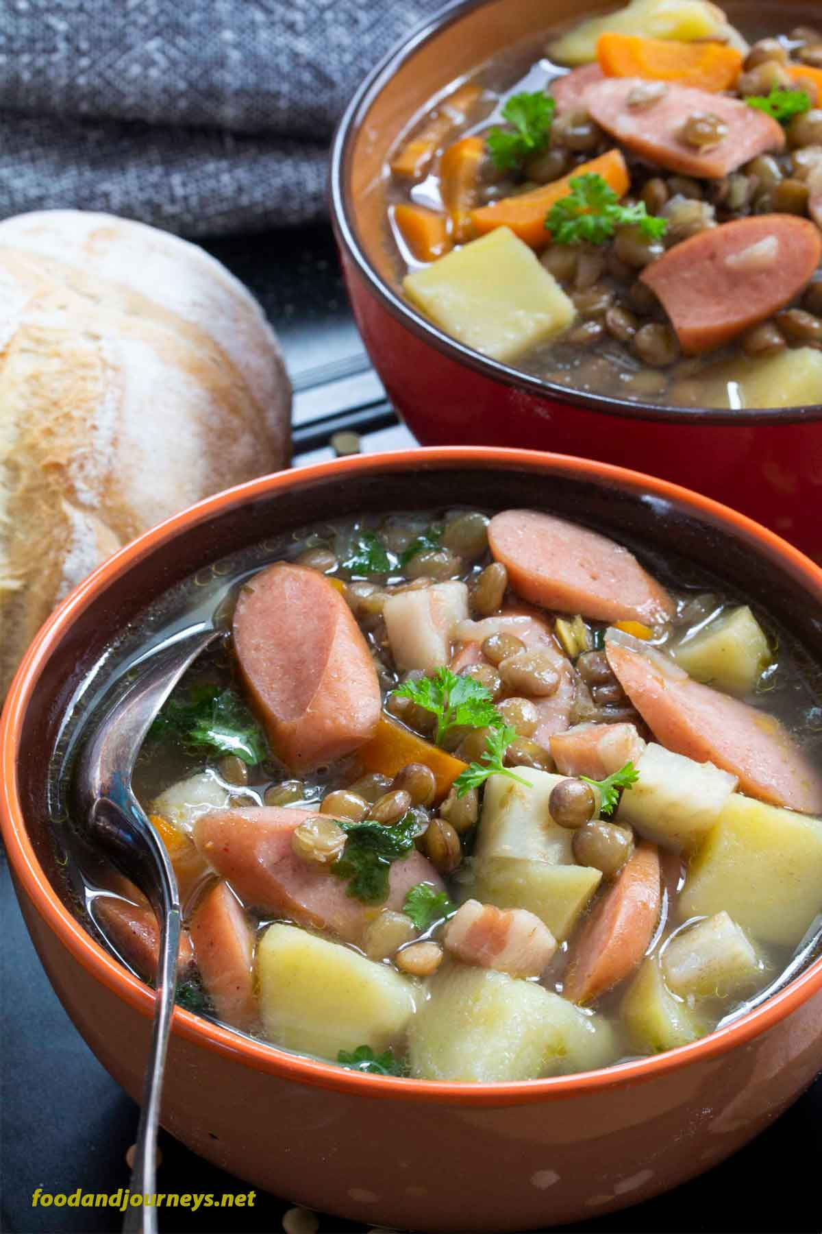 Two bowls of German Lentil Soup with Frankfurters are served, with some bread and wine. A vegetable soup that can also be eaten on its own, as a full meal. One of those easy soup recipe to have around when the weather gets chilly!