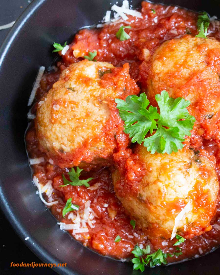 A serving of Italian Bread & Cheese Dumplings served on tomato sauce. If you're running out of ideas to use stale bread, this dumpling recipe is a good one to try. For sure, it will turn out to be one of your favorite Italian appetizers!