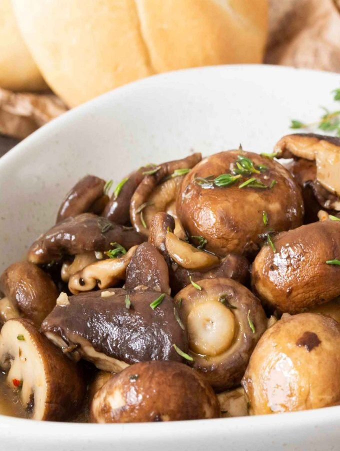 Closer shot at a plate of Mixed Mushrooms with White Wine, with some bread rolls on the side.