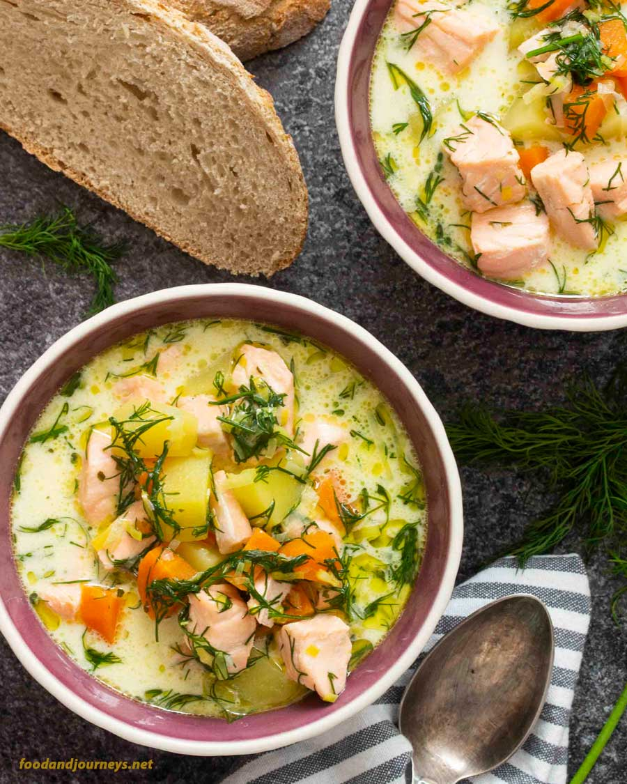 Overhead shot of two bowls of Finnish Salmon Soup (Lohikeitto), with some slices of bread on the side; an easy fish soup recipe!