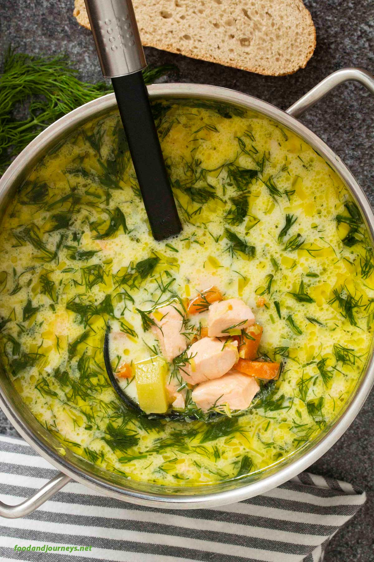 An overhead shot of a pot of finnish salmon soup, highlighting the pieces of salmon, ready for serving.