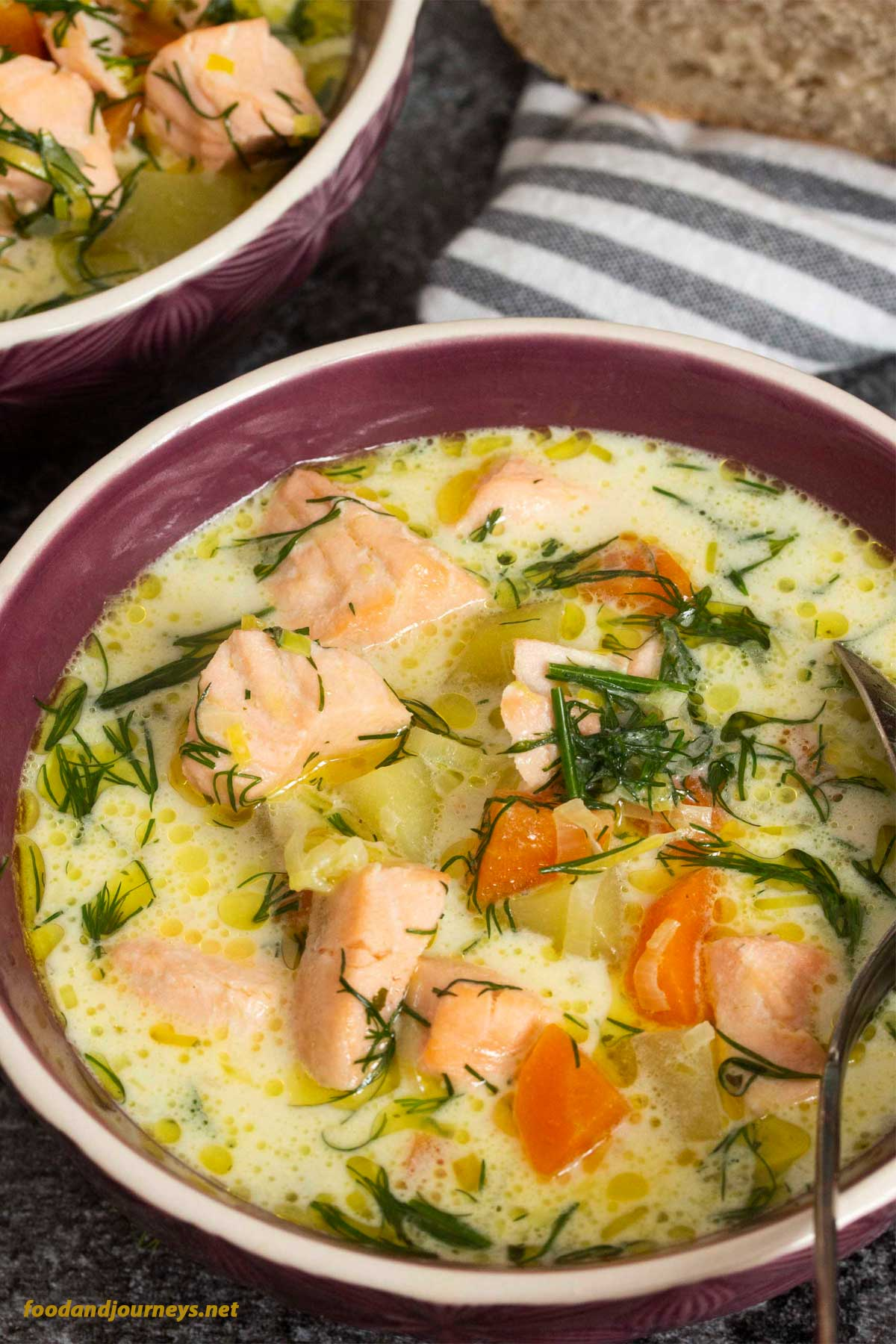 A closer shot of a bowl of Finnish Salmon Soup (Lohikeitto), focusing on the bits of salmon and vegetables in the soup.