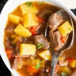 A serving of German Goulash Soup up close; highlighting the beef and vegetables in this hearty soup. Slightly lighter than a stew, this beef soup recipe is best served with bread rolls and some wine.
