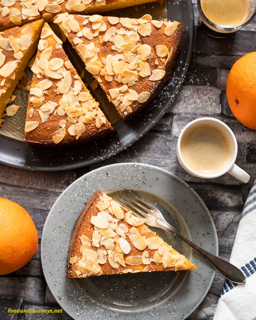 A slice of French Orange and Almond Flourless cake on a plate served with a shot of espresso. Oranges and the rest of the cake on a baking tray are also on the same table.