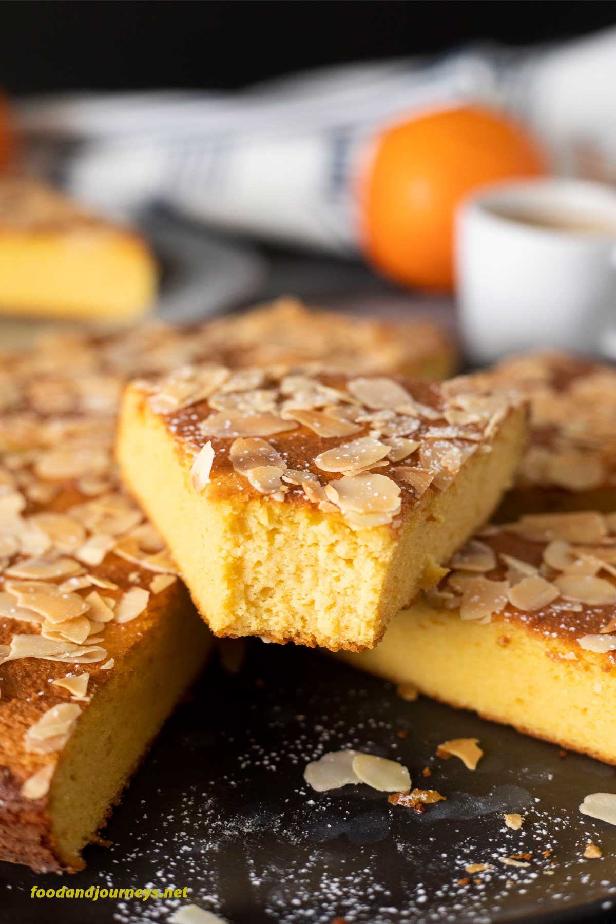 A slice of French Orange and Almond Cake is placed on top of the rest of the cake. The texture of the cake is highlighted, as well as the undeniable orange color of the inside of this flourless cake.