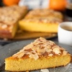 A slice of French Orange and Almond Flourless Cake on top of the rest of the cake. The texture of the cake is highlighted in this image, as well as the undeniable orange color of the inside of the flourless cake.