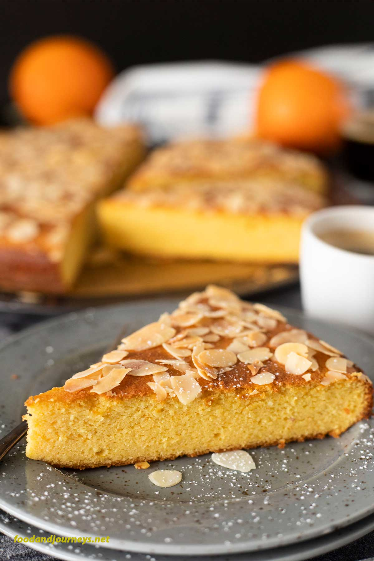 A slice of French Orange and Almond Flourless Cake placed on a plate, ready for serving, with a shot of espresson. The rest f the cake is on the background, as well as a couple of whole oranges.