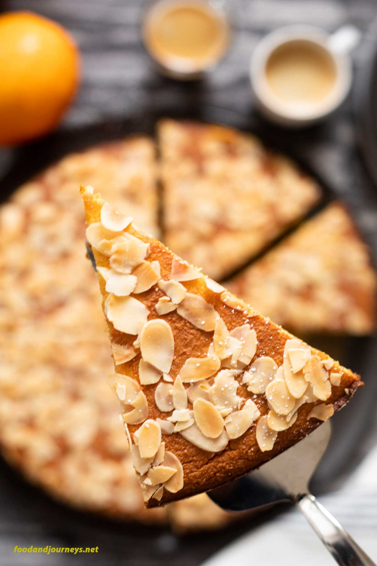 A slice of French Orange and Almond Flourless cake is being lifted from the baking tray, about to be served. The image highlights the crunchy its of sliced almonds on top of the orange cake.