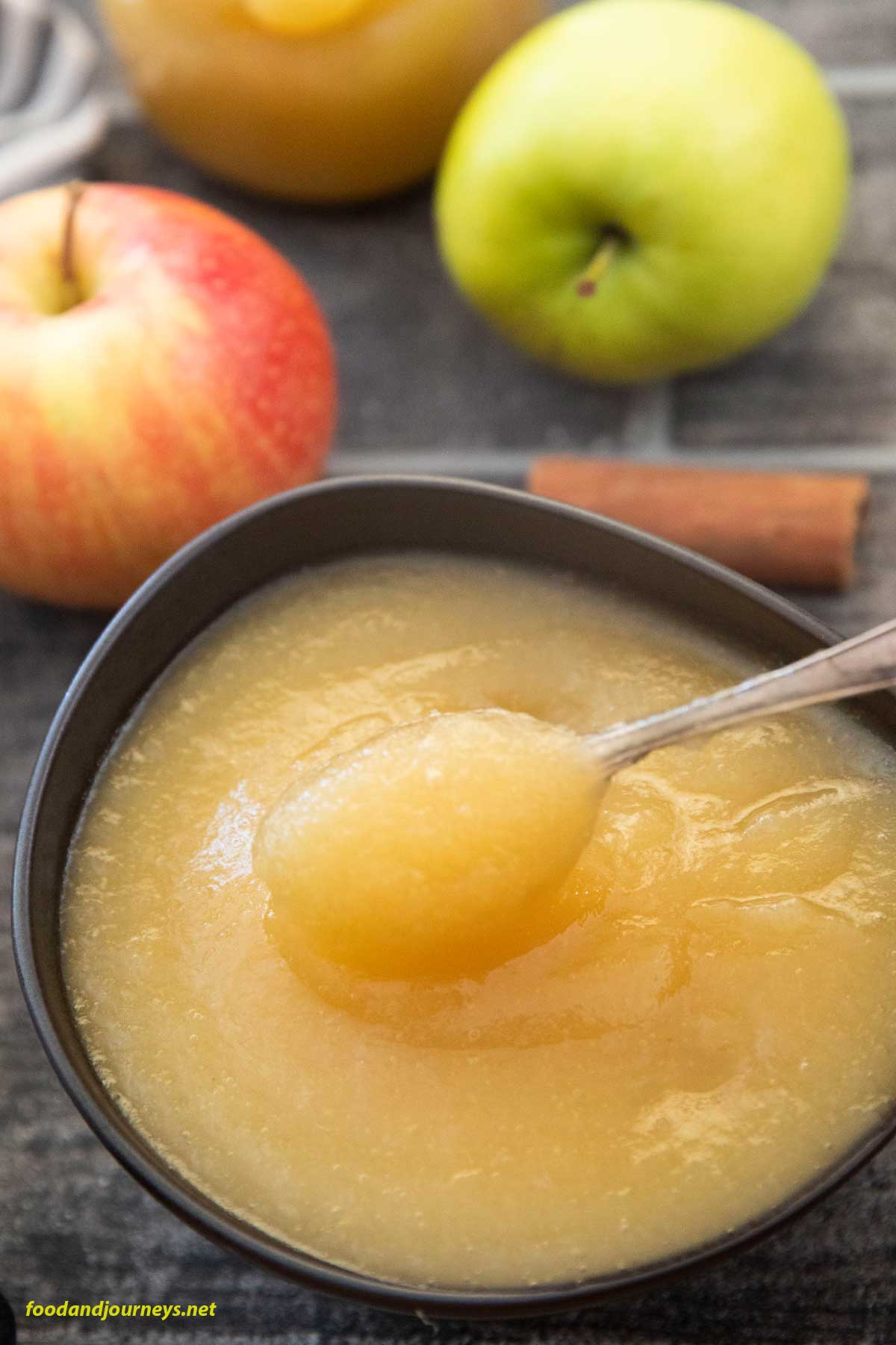 An overhead shot of apfelmus in a bowl, ready for serving, with a half stick of cinnamon and some apples on the side.