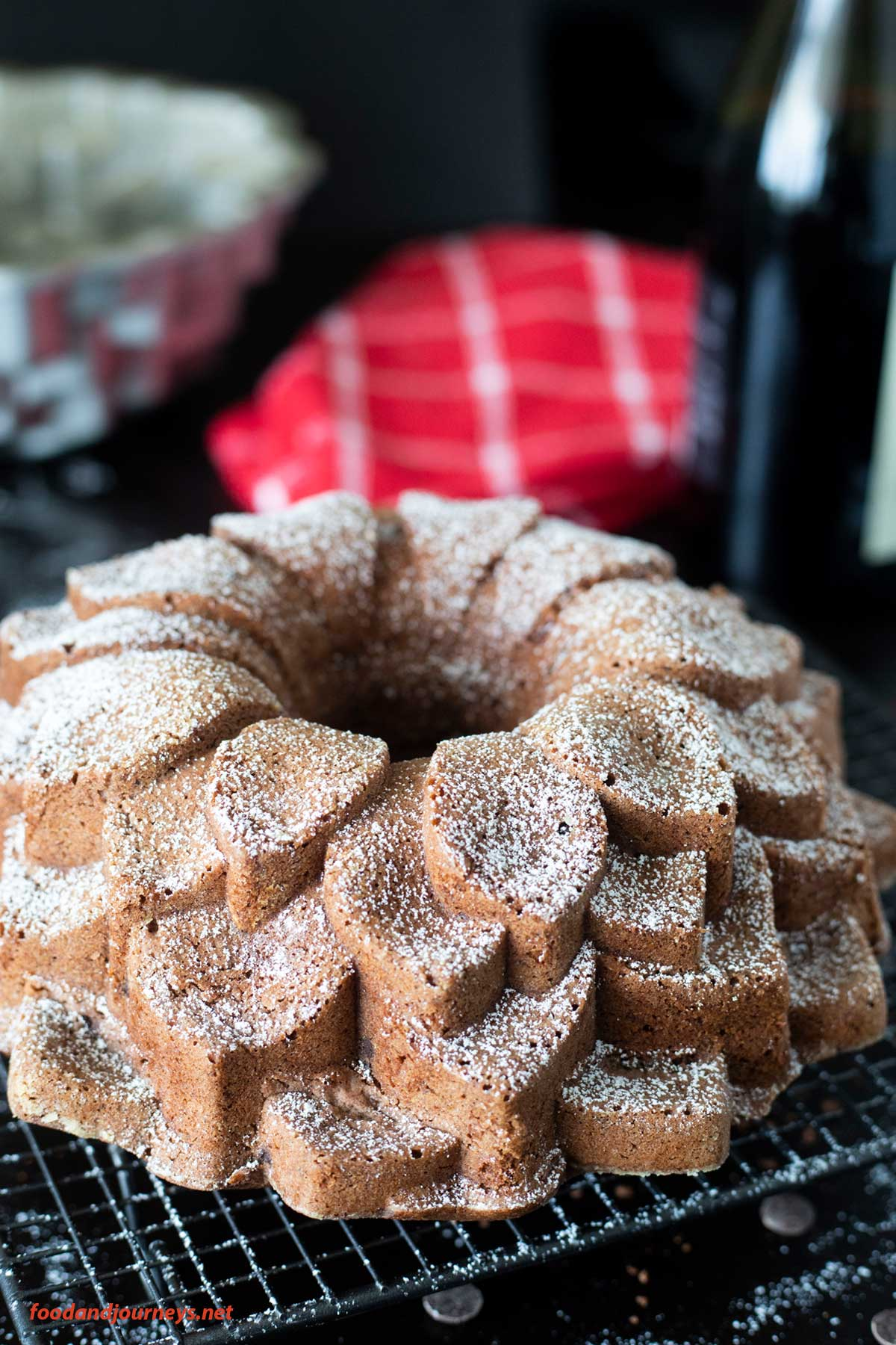 A side shot of German Red Wine and Chocolate Cake, cooling on a rack and dusted with powdered sugar.