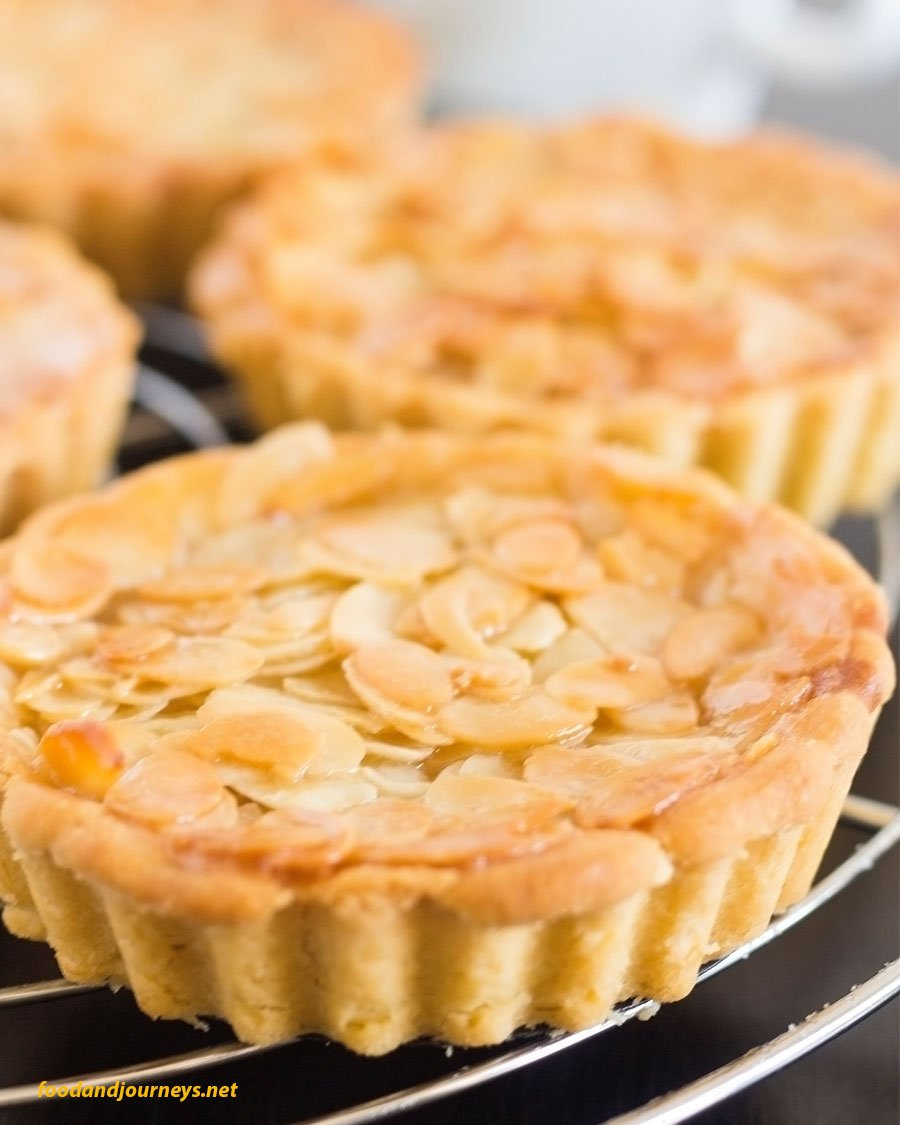 A closer shot of Swedish Almond Tart (Toscabit) on a cooling rack, highlighting the caramelized almonds on top, as part of Swedish Food Recipes You Must Try