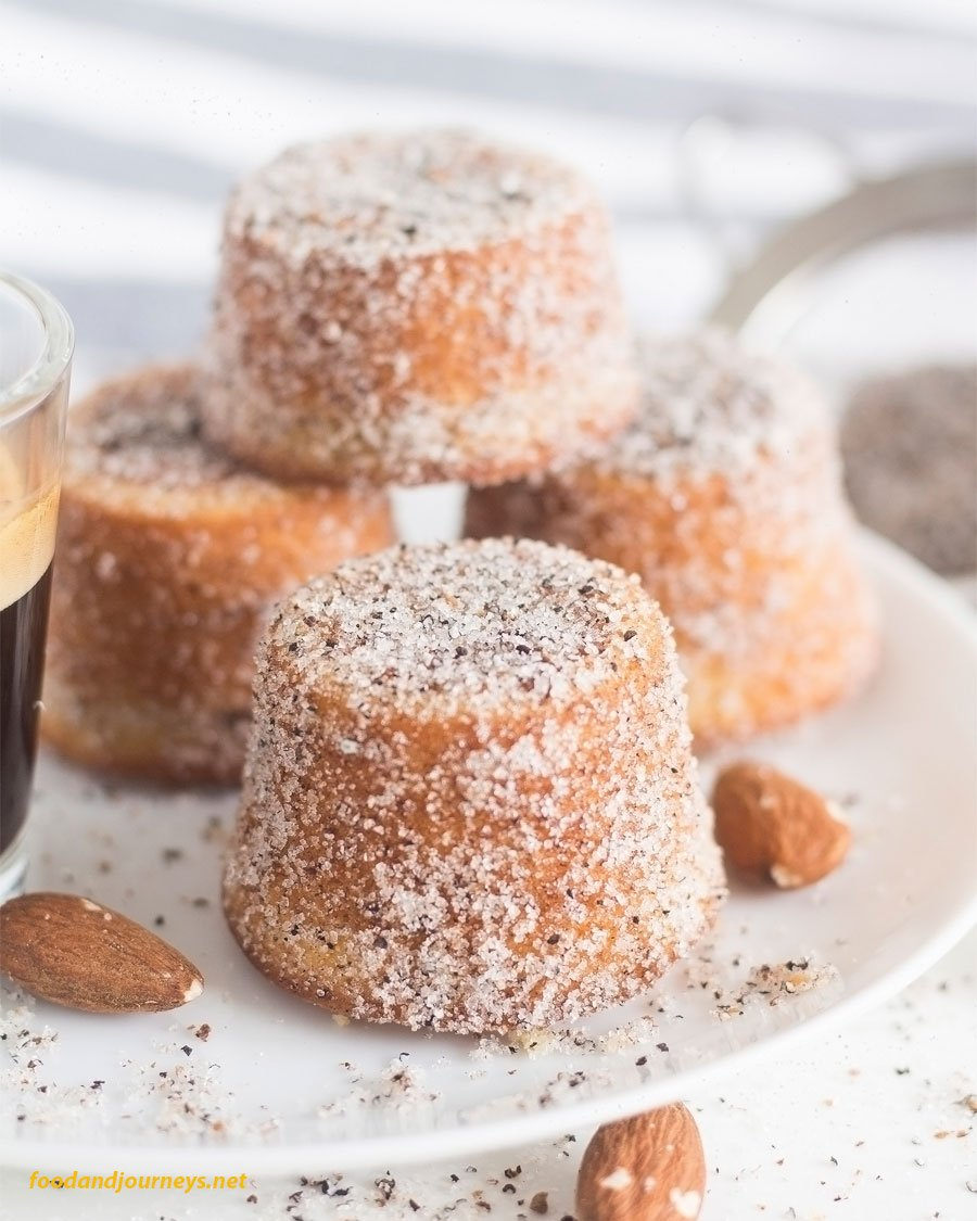 Swedish Almond & Cardamom Mini Cakes on a plate, dusted with more cardamom and sugar, as part of Swedish Food Recipes You Must Try