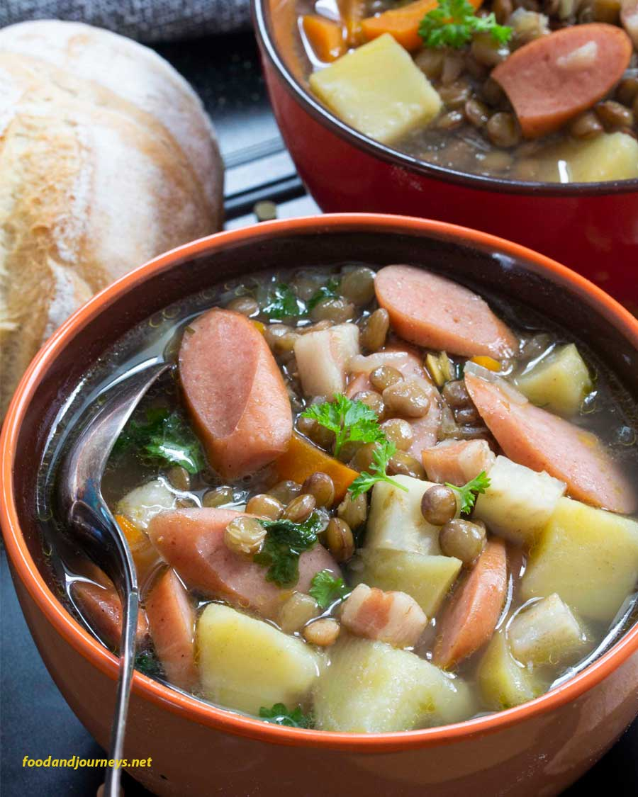 A closer shot to a bowl of German Lentil Soup with Frankfurters, highlighting the sausage and chunks of vegetables in the bowl.