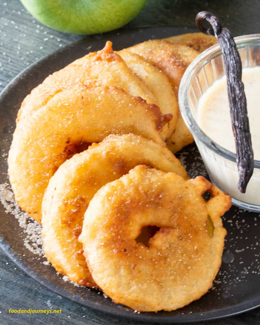 German Apple Fritters (Apfelkuchle) arranged on a plate, ready for serving, with vanilla sauce on the side.