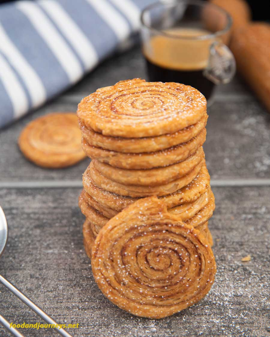 A stack of Puff Pastry Pinwheel Cookies, sprinkled with powdered sugar and served with an espresso.