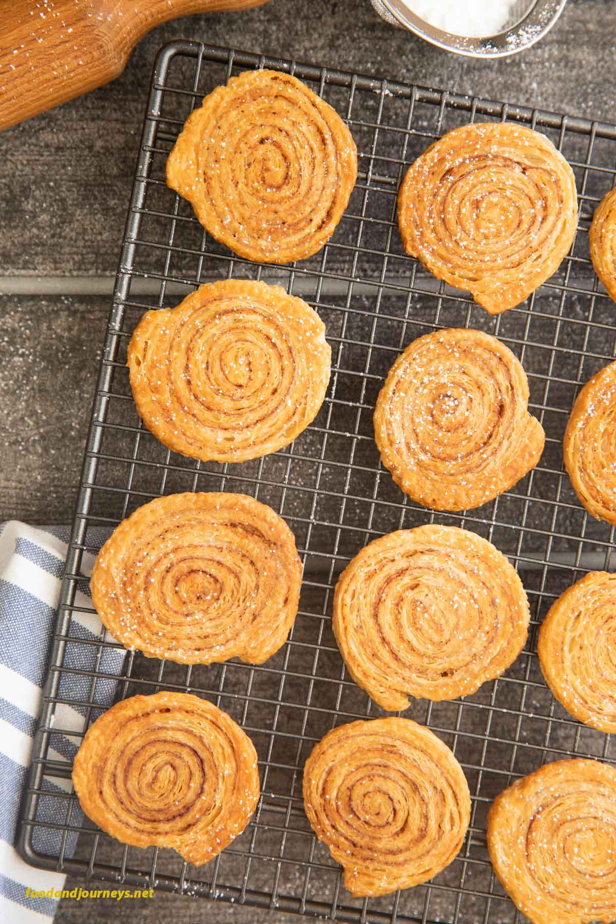 An overhead shot of freshly baked Puff Pastry Pinwheel Cookies on a cooling rack.