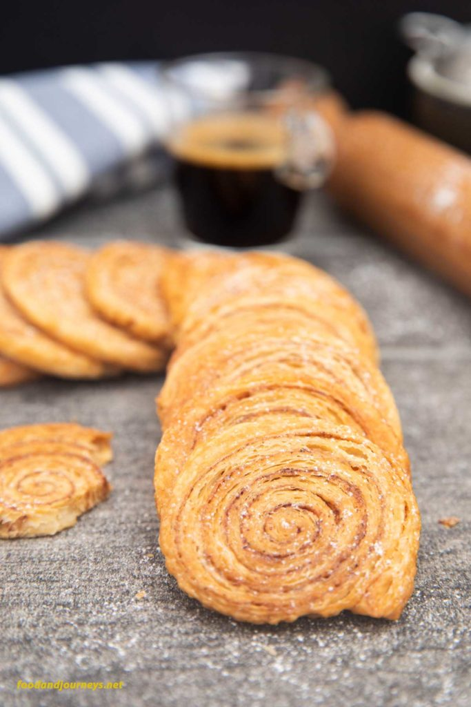 A roll of Puff Pastry Pinwheel Cookies set on a table, with the rolling pin and a shot of espresso on the side.