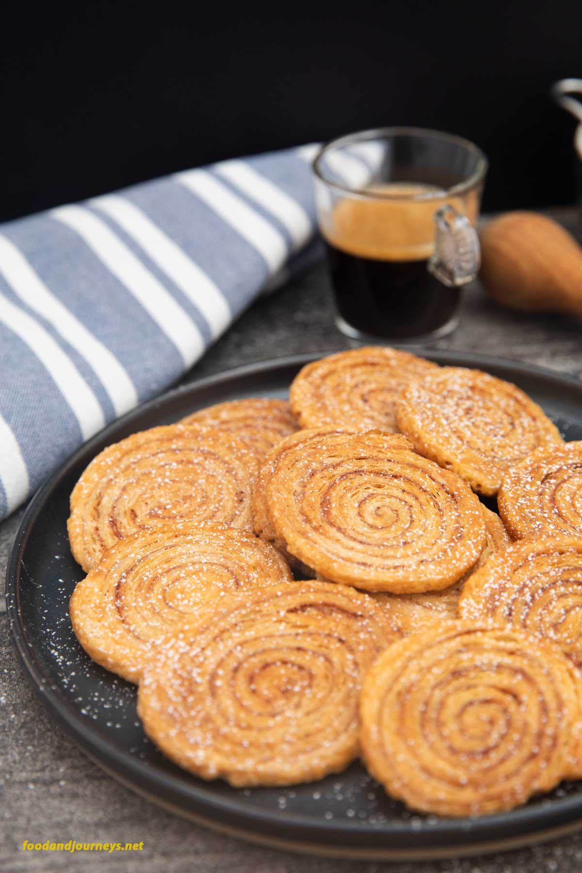 A plate full of freshly baked Pinwheel Cookies, sprinkled with sugar, ready for serving.