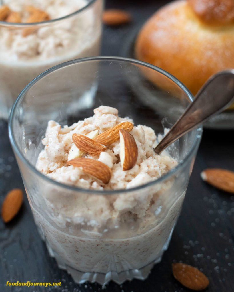 Two servings of Sicilian Almond Granita, with slices of almonds on top, and served with Sicilian Brioche.
