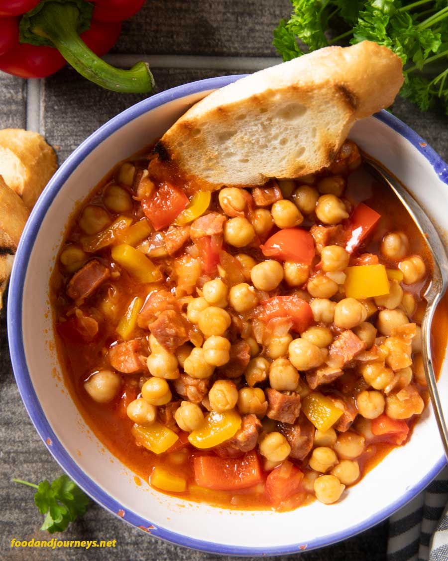Cornerstone image for Spanish Chorizo and Chickpea Stew, an overhead shot of a serving, with some toasted bread on the side.