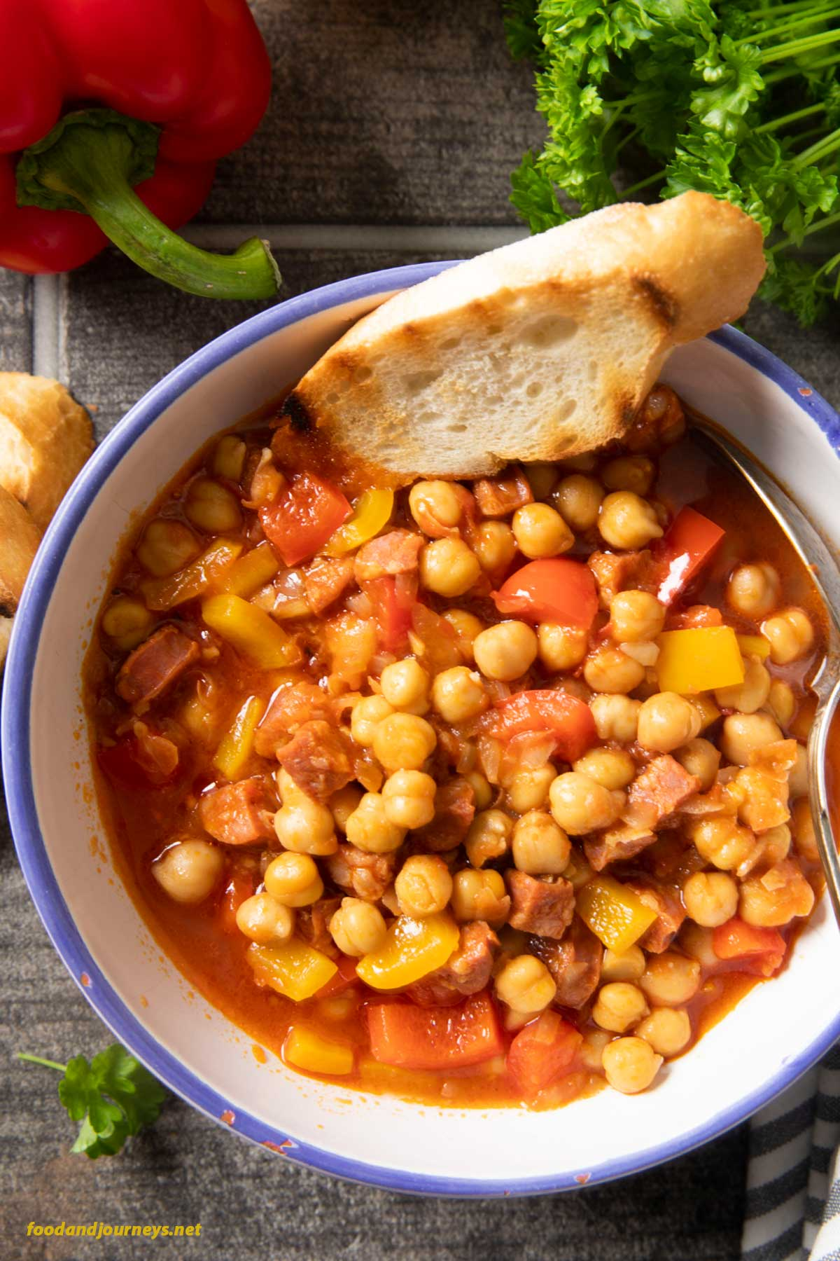 An overhead shot of a bowl of Spanish Chorizo and Chickpea Stew, served with a slice of toasted bread, more bread on the side of the bowl.