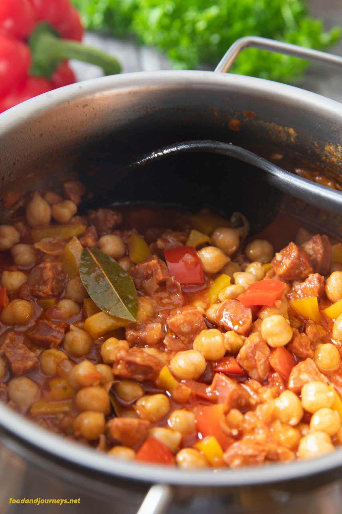 A closer shot of a pot of Spanish Chorizo and Chickpea Stew, highlighting the lovely color of the dish, as well as the dried bay leaf on top.