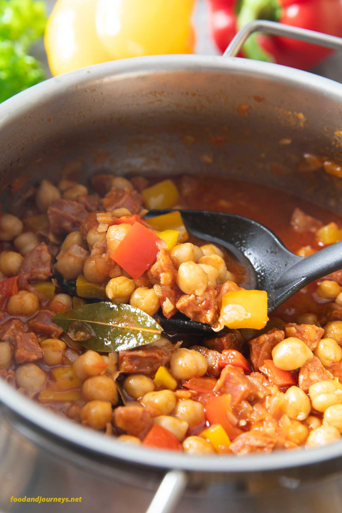 A closer shot of a pot of Spanish Chorizo and Chickpea Stew, with someone using a ladle to scoop and place it on a plate for serving.