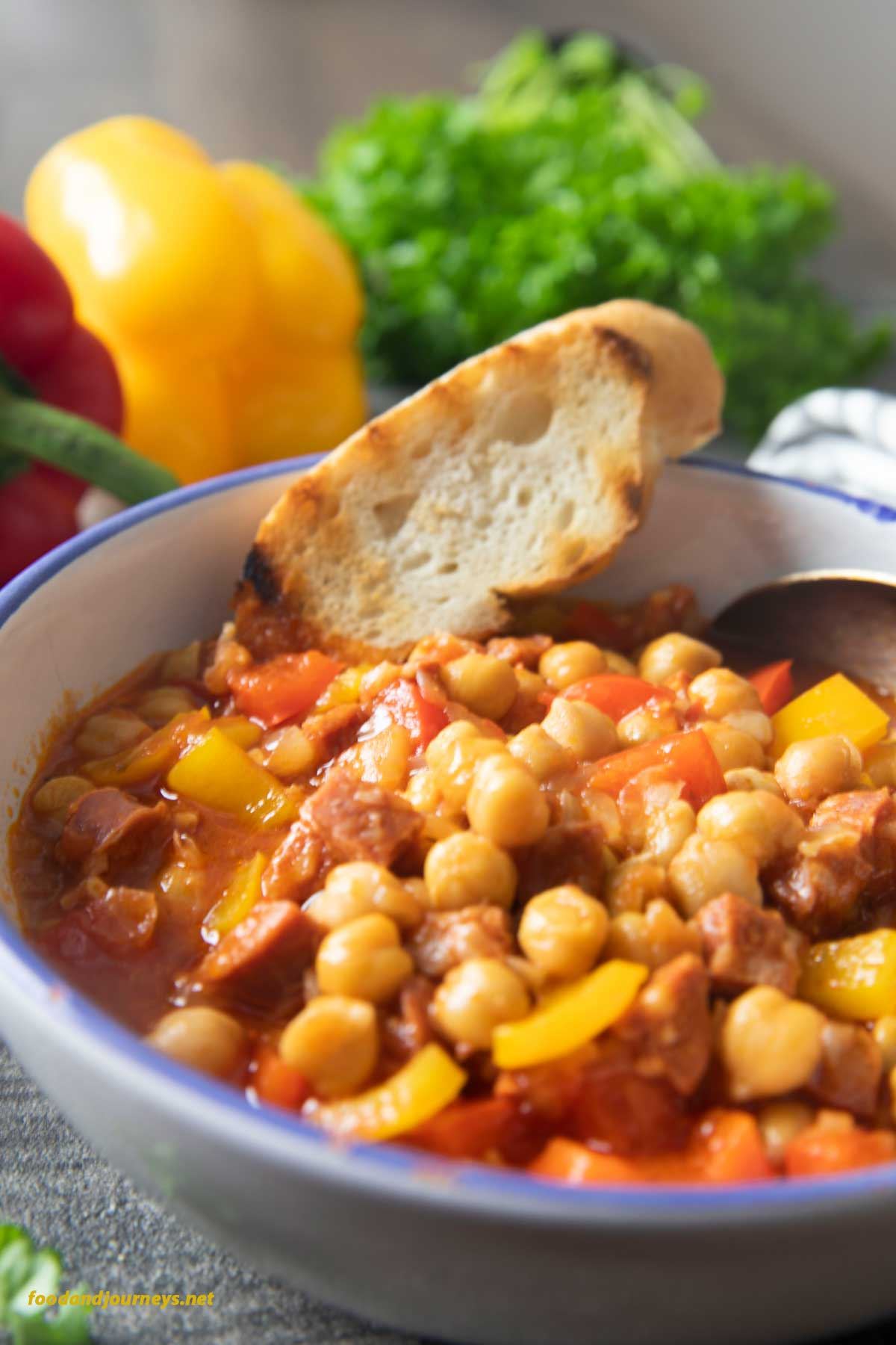 A closer shot of a bowl of Chorizo and Chickpea Stew, with a piece of toasted bread. A bunch of parsley is on the background, an option for serving.