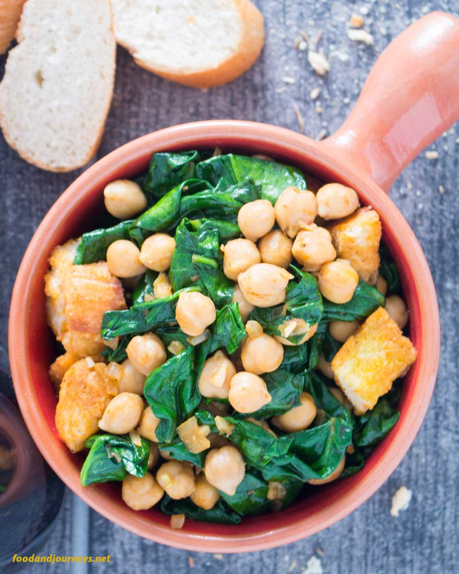 An overhead shot of a serving of Spanish Spinach with Chickpeas, with slices of bread on the side.