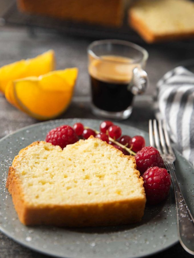 A slice of French Yogurt Cake, with berries on the side and slices of orange and an espresso.