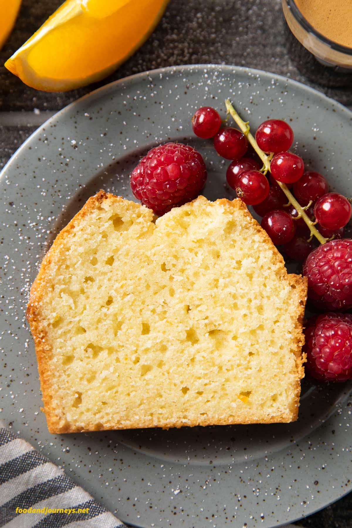 An overhead shot of a slice of orange yogurt cake, served with some berries.