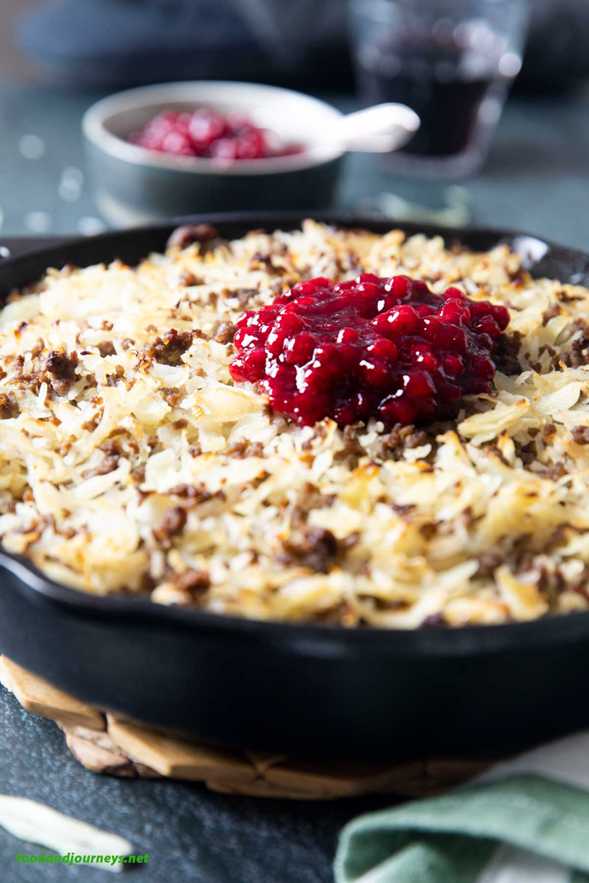 A closer shot of a skillet of Ground Beef & Cabbage Casserole, with lingonberry jam on top.