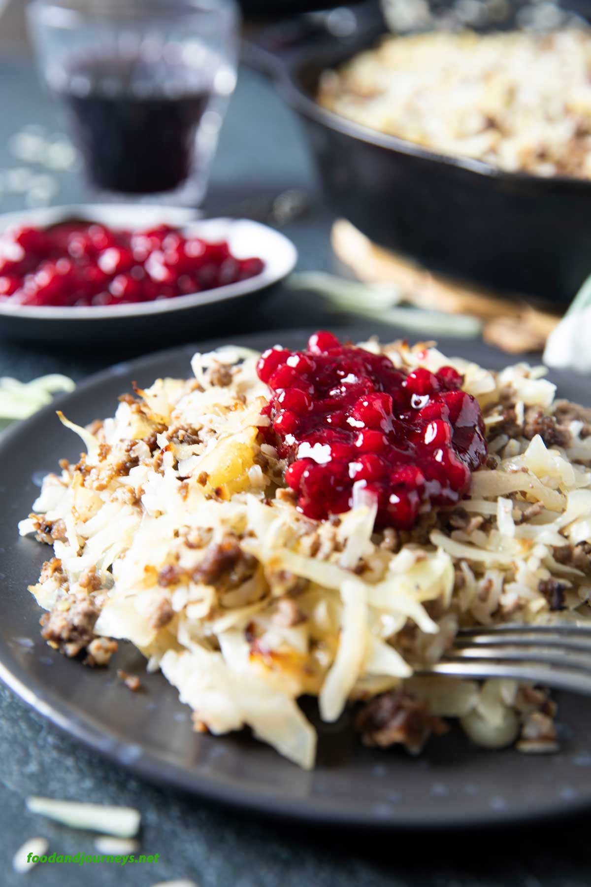 A serving of Finnish Ground Beef & Cabbage Casserole, with some lingonberry jam on top, and more on the side.