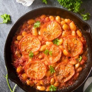 An overhead shot of a skillet with just cooked Greek Baked Giant Beans, with a bunch of parsley on the side, and some onion skins.