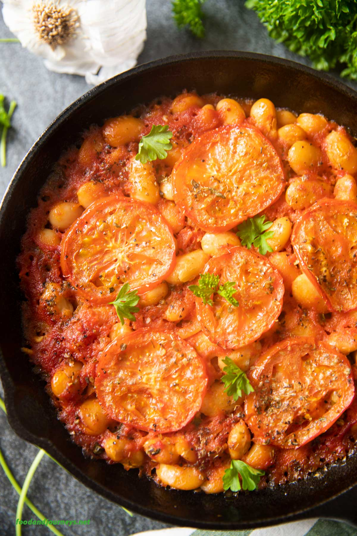 An overhead and closer shot of a pan of Beans in Tomato Sauce, highlighting the baked slices of tomatoes on top.